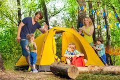 投一个帐篷的愉快的家庭在森林里 免版税图库摄影