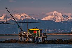 投下净渔小屋在日落反对有雪的,小游艇船坞二比萨,托斯卡纳,意大利阿尔卑斯 免版税库存照片
