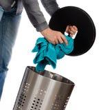 投入一块肮脏的毛巾的年轻人在洗衣篮 免版税库存图片
