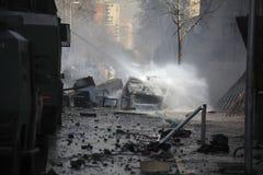 投入一辆灼烧的汽车用水在一条被击毁的街道 免版税库存图片