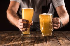 投入两个杯子用与泡沫的新鲜的啤酒的人的播种的图象在木 免版税库存照片