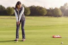 投入为孔的高尔夫球运动员 免版税库存照片