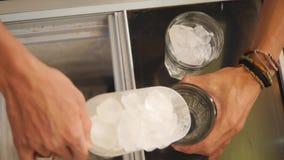 投入冰块的瓢Barista在玻璃 准备轻的夏天鸡尾酒起点  4K,慢动作 股票视频