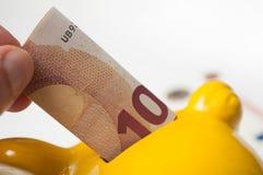 投入十欧元钞票的人的手在黄色pi 免版税库存照片