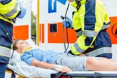 投入受伤的男孩的紧急医生在救护车 免版税库存照片