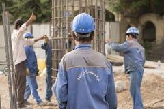 投入圆柱形金属结构的建筑工人在Plac 库存照片