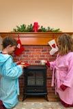 投入圣诞老人牛奶和曲奇饼的孩子 免版税库存照片