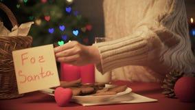 投入圣诞老人的女孩笔记在杯牛奶和传统圣诞节曲奇饼附近 影视素材