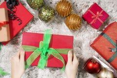 投入圣诞节礼物的少妇 免版税图库摄影