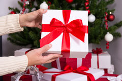 投入圣诞节礼物箱子的男性手在圣诞树下 免版税库存照片
