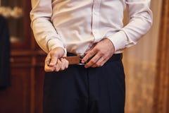 投入在传送带、时尚和衣物概念,新郎的商人准备好早晨在仪式前 免版税库存照片