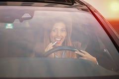投入在唇膏的美丽的妇女在汽车 免版税库存图片