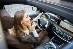 投入在唇膏的美丽的妇女在汽车 库存图片