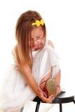 投入在她的鞋子的逗人喜爱的小女孩白色礼服 库存图片