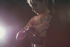 投入在拳击手套的女性战斗机prepairing为训练 免版税库存图片