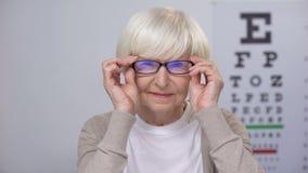 投入在新的眼镜和看对凸轮,改善的愉快的女性退休人员 股票录像