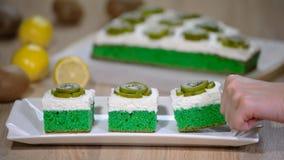 投入在白色与纯奶油的板材绿色软的蛋糕和冠上与猕猴桃 股票录像