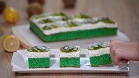 投入在白色与纯奶油的板材绿色软的蛋糕和冠上与猕猴桃 股票视频