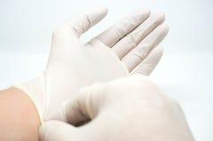 投入在白色背景的一次性不育的白色手套 免版税库存图片