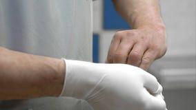 投入在白色被消毒的外科手套的医生 免版税图库摄影