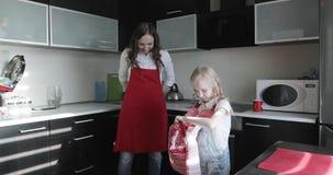 投入在红色围裙的一个年轻母亲和她的女儿在厨房 股票录像