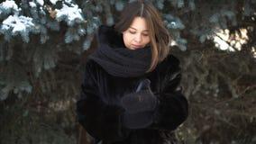 投入在绿色云杉的背景的被编织的手套的毛皮大衣和大,黑围巾的美女 温暖的女孩 图库摄影