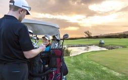 投入在绿色的高尔夫球夫妇 免版税库存图片