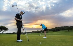 投入在绿色的高尔夫球夫妇 图库摄影