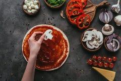 投入在薄饼面团上的妇女播种的射击蘑菇切片在薄饼上 库存图片