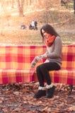 投入在长凳的一副手套的年轻美丽的妇女在公园 免版税库存照片