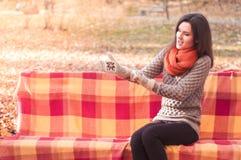 投入在长凳的一副手套的年轻美丽的妇女在秋天公园 库存图片