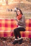 投入在长凳的一副手套的年轻美丽的妇女在秋天公园 图库摄影