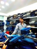 投入堆服装的店主在costumers前,印多尔, MP,印度 免版税库存图片