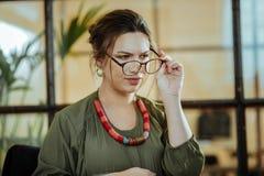 投入她的玻璃的年轻兴旺的女实业家  免版税库存照片