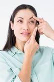 投入她的隐形眼镜的浅黑肤色的男人 免版税库存照片