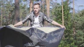 投入帐篷的年轻人在单独放松杉木森林有胡子的人户外 与狂放的自然的团结 ??  影视素材