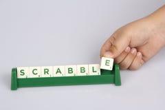 投入拼字游戏E信件瓦片的孩子的手 免版税库存照片