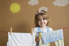 投入晒衣夹的小的俏丽的女孩手和停留烘干衣裳 概念性家事 婴孩帮助妈妈 免版税库存照片