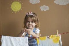 投入晒衣夹的小的俏丽的女孩手和停留烘干衣裳 概念性家事 婴孩帮助妈妈 免版税库存图片