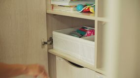 投入有婴孩衣裳的妇女箱子在衣橱 影视素材