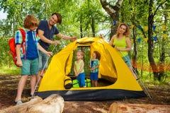 投入有孩子的帐篷的父母在野营 免版税库存照片