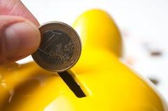 投入欧元硬币的人的手在黄色存钱罐o中 免版税库存图片