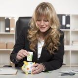 投入欧洲金钱的女实业家在存钱罐中 免版税库存照片