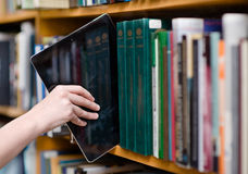 投入片剂个人计算机的特写镜头手在架子在图书馆里 图库摄影