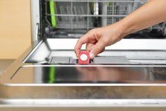 投入片剂的妇女在洗碟机用洗涤剂箱子 库存照片