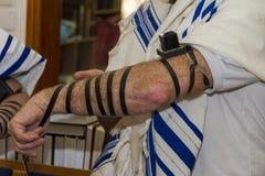 投入犹太Tefillin在他的胳膊和穿祈祷的一个成人人晨祷披巾 免版税库存照片
