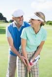 投入球的打高尔夫球的夫妇一起微笑对照相机 图库摄影