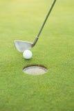 投入球的高尔夫俱乐部在孔 免版税库存照片