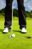 投入球的高尔夫球运动员在孔 免版税库存照片