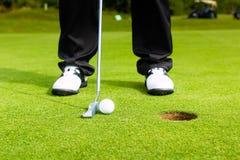 投入球的高尔夫球运动员在孔 免版税库存图片